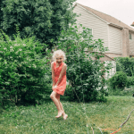 girl playing in backyard in the summer
