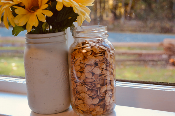 mason jar filled with roasted pumpkin seeds by painted mason jar with sunflowers sitting on windowsill