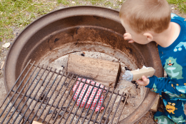 little boy starting a fire with fire starters