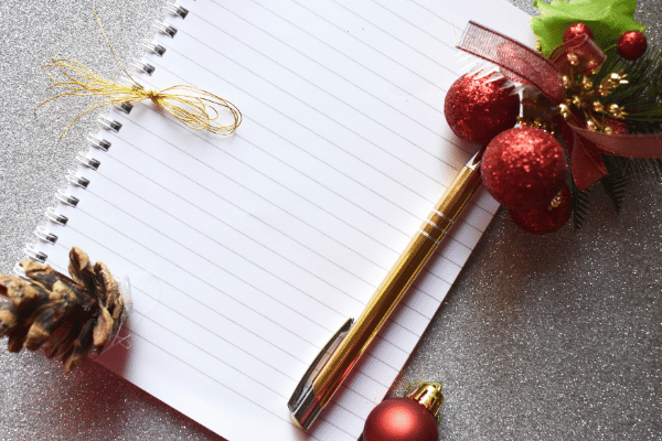 blank paper notebook with christmas ribbon, gold pen and decorations